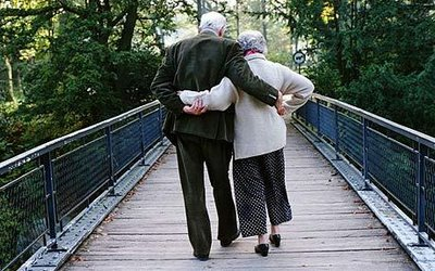 Elderly couple walking across footbridge Photo GETTY